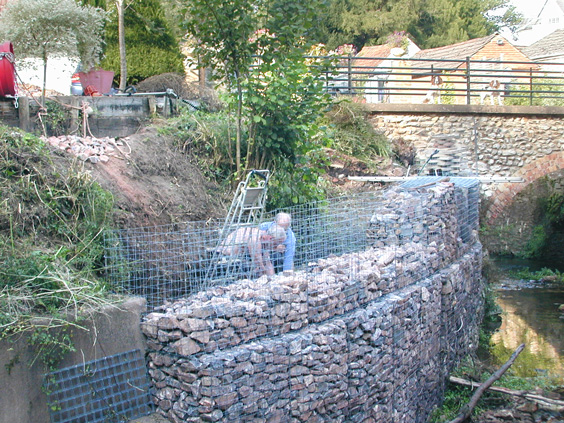 people installing a gabion wall